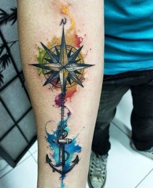 Colourful anchor and compass tattoo on forearm