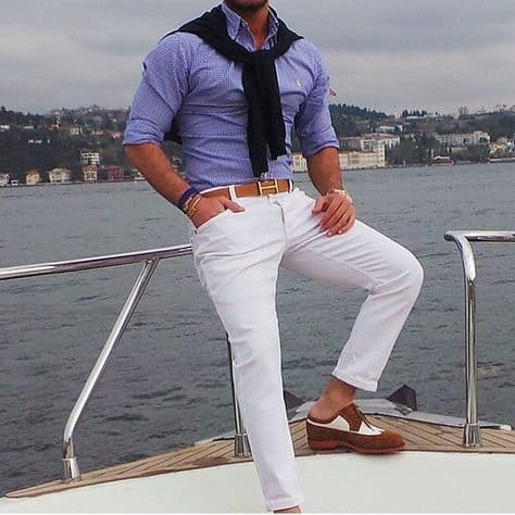 stylish man sat on a yacht wearing nautical clothes